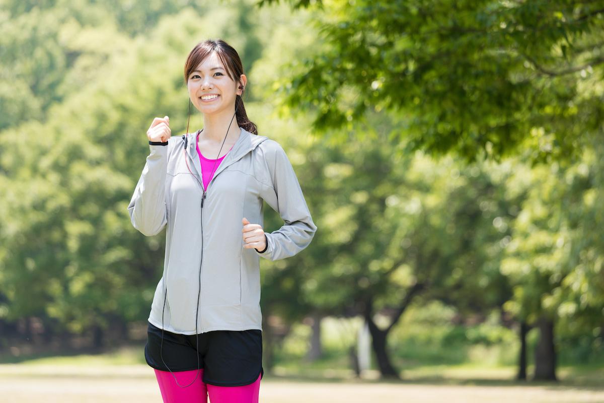 公園でジョギングするスポーティーな女性